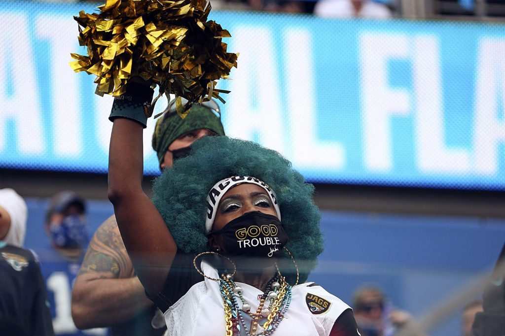 A fan with a social justice mask cheers during the first half of an NFL football game between the Jacksonville Jaguars and the Indianapolis Colts, Sunday, Sept. 13, 2020, in Jacksonville, Fla. (AP Photo/Stephen B. Morton)