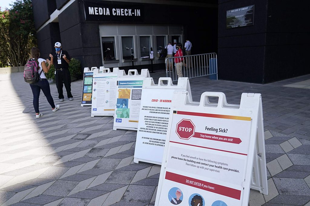 Members of the media arrives for a health screening before an NFL football game between the Carolina Panthers and the Las Vegas Raiders Sunday, Sept. 13, 2020, in Charlotte, N.C.. (AP Photo/Brian Blanco)