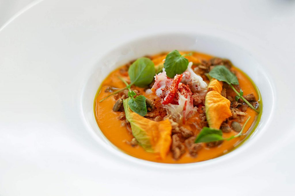 Alaskan King crab with chilled heirloom tomato soup, fennel, granola, and wild watercress.