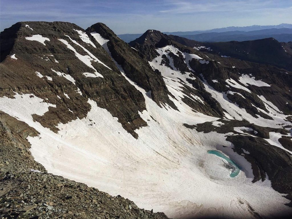 An ample snowfield exists on the lower slopes of Conundrum Peak in July 2019. Many hikers on Castle Peak traverse to the summit of Conundrum.