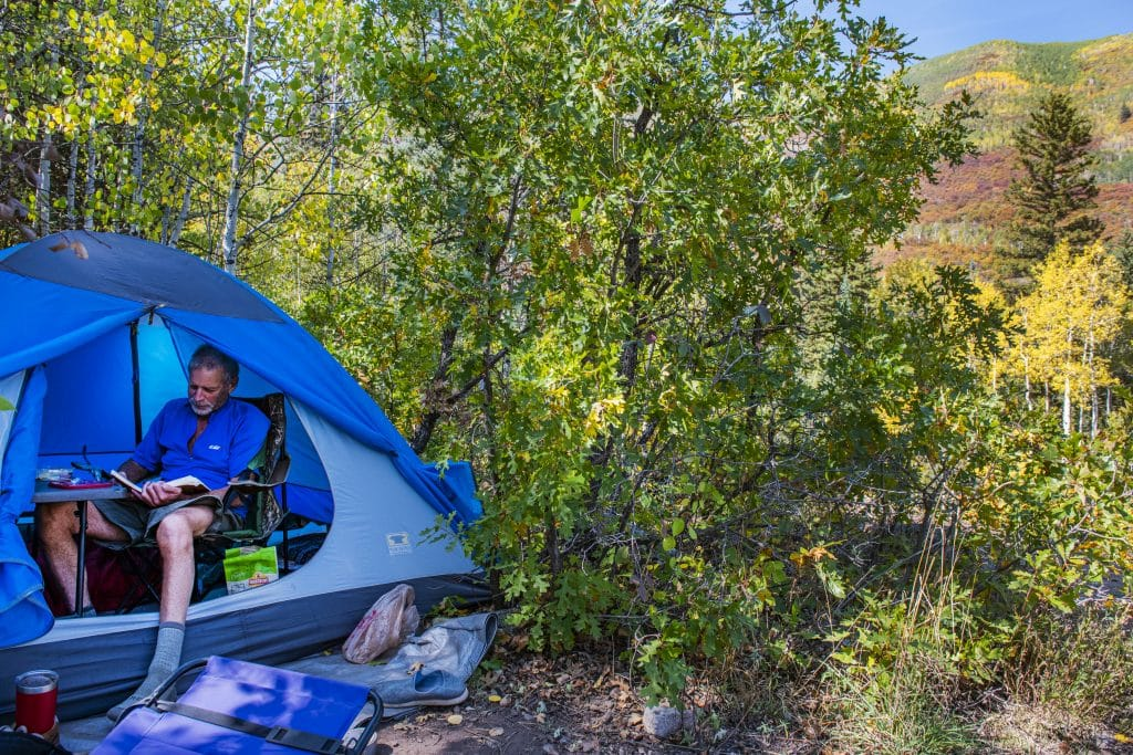 Will Kesler reads a book in his tent on a fall day in Snowmass on Wednesday, Sept. 23, 2020. Kesler has lived in the valley for forty years. For the past year and a half he's been living in his tent and traveling while writing a book.