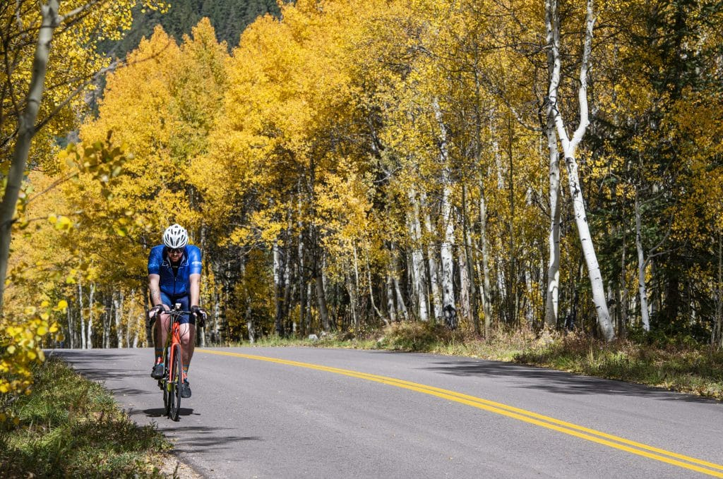 A road biker takes a scenic ride through the changing leaves on Castle Creek Road in Aspen on Wednesday, Sept. 23, 2020.