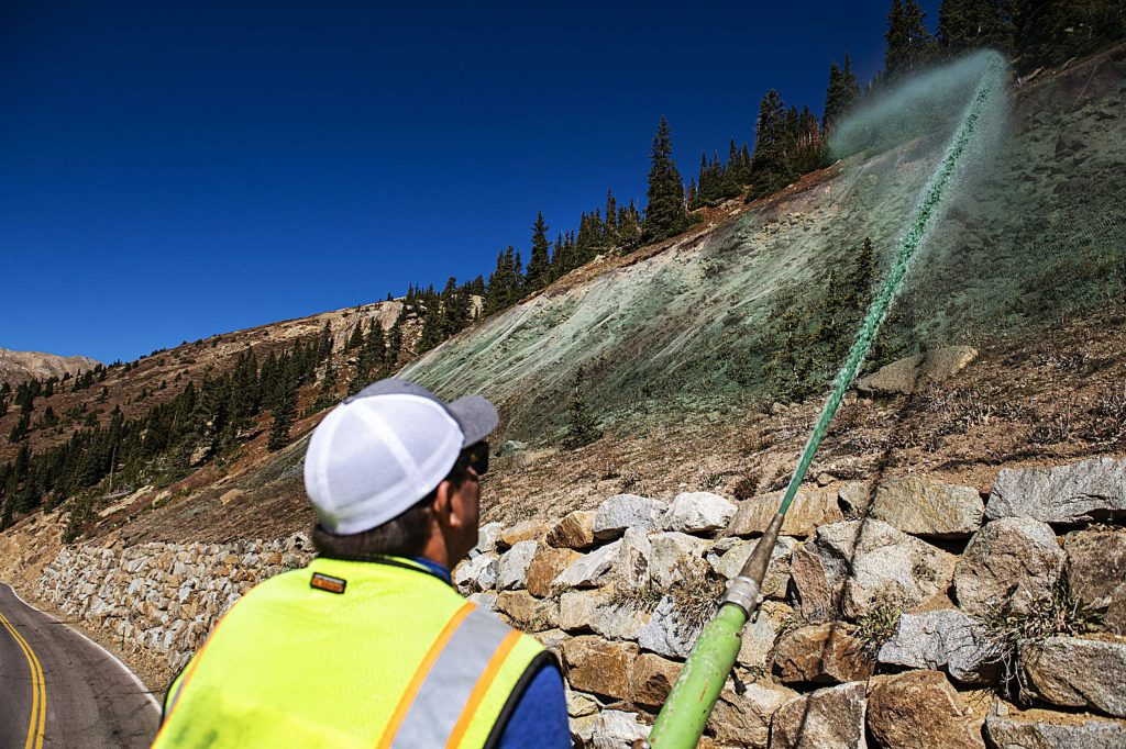 Todd Sutton sprays the side of Independence Pass with colored wood mulch on Wednesday, Sept. 30, 2020. There are areas of the pass that are being sprayed to help with revegetation of eroded areas.