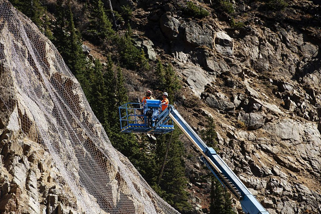 Workers use a boom to work on the rock fall mesh for mitigation on Independence Pass on Wednesday, Sept. 30, 2020.