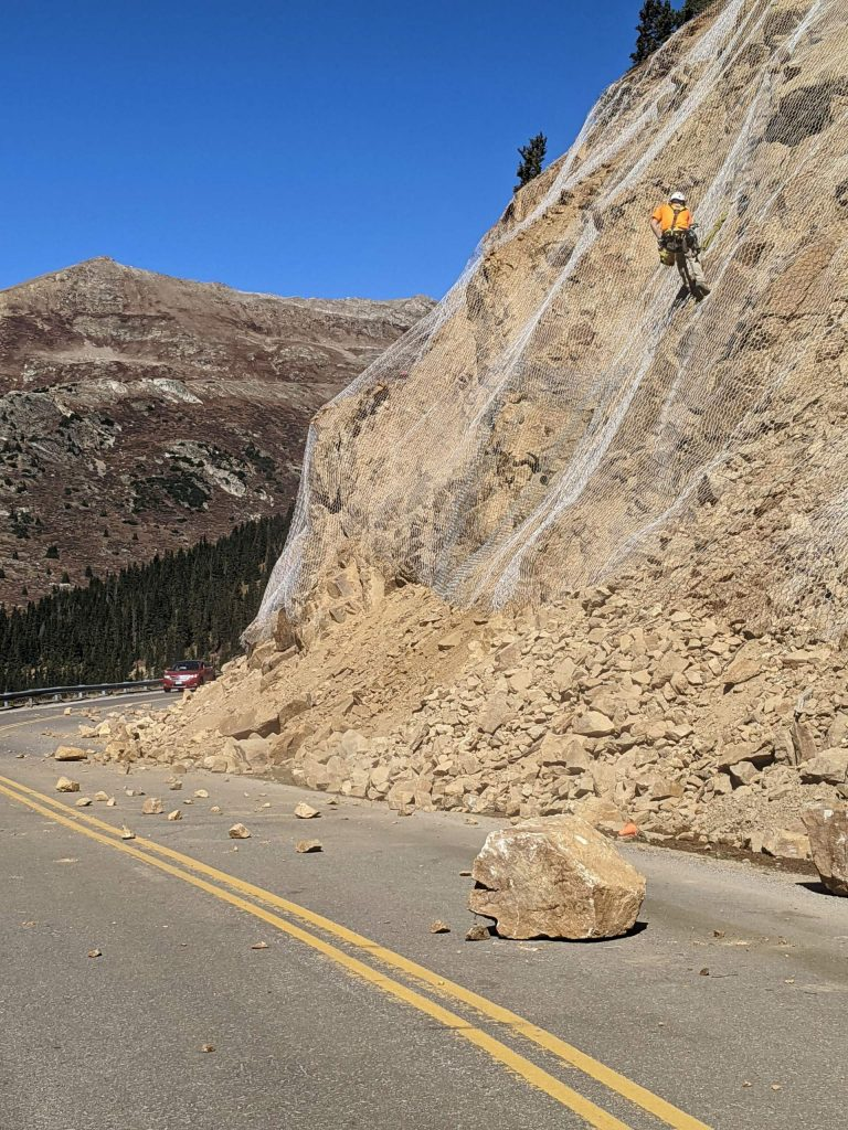 A worker for a CDOT contractor pries rocks loose Wednesday from the Top Cut near the summit of Independence Pass. Highway 82 was closed during the day to protect travelers.