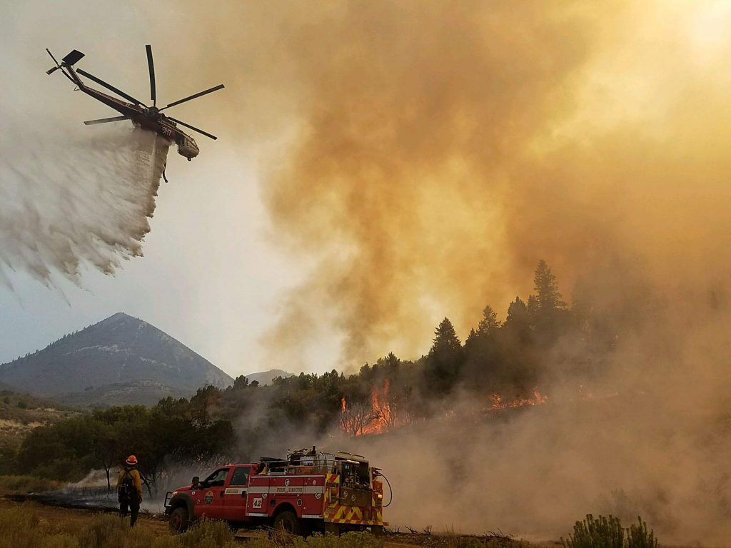 A helicopter helps with fire suppression on the Pine Gulch Fire burning near Grand Junction.