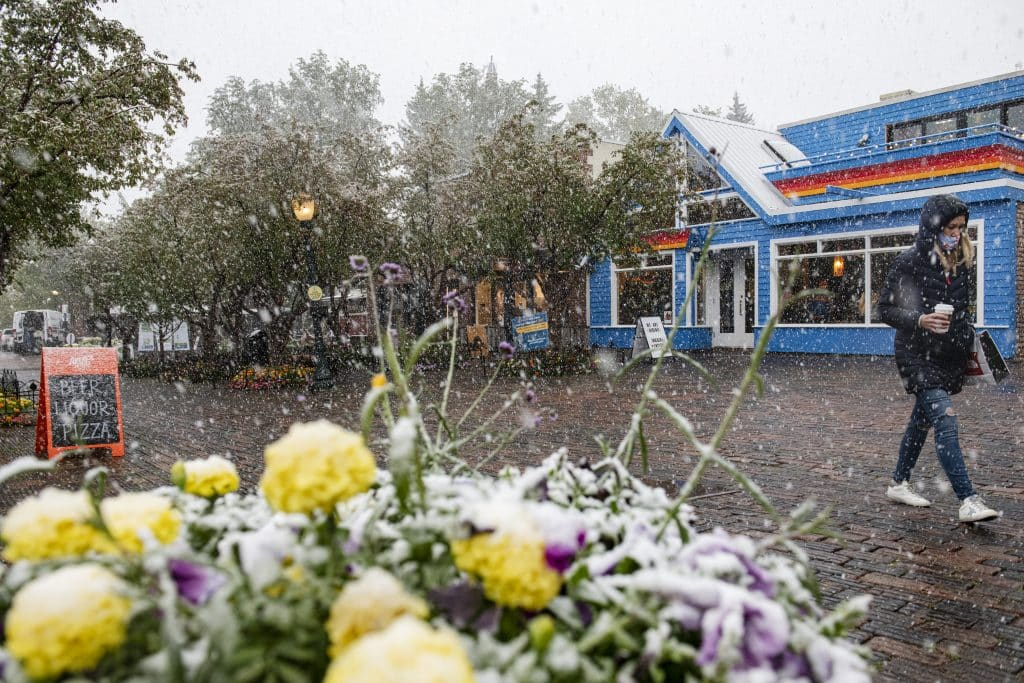 A woman walks through a snowstorm in downtown Aspen on Tuesday, Sept. 8, 2020.