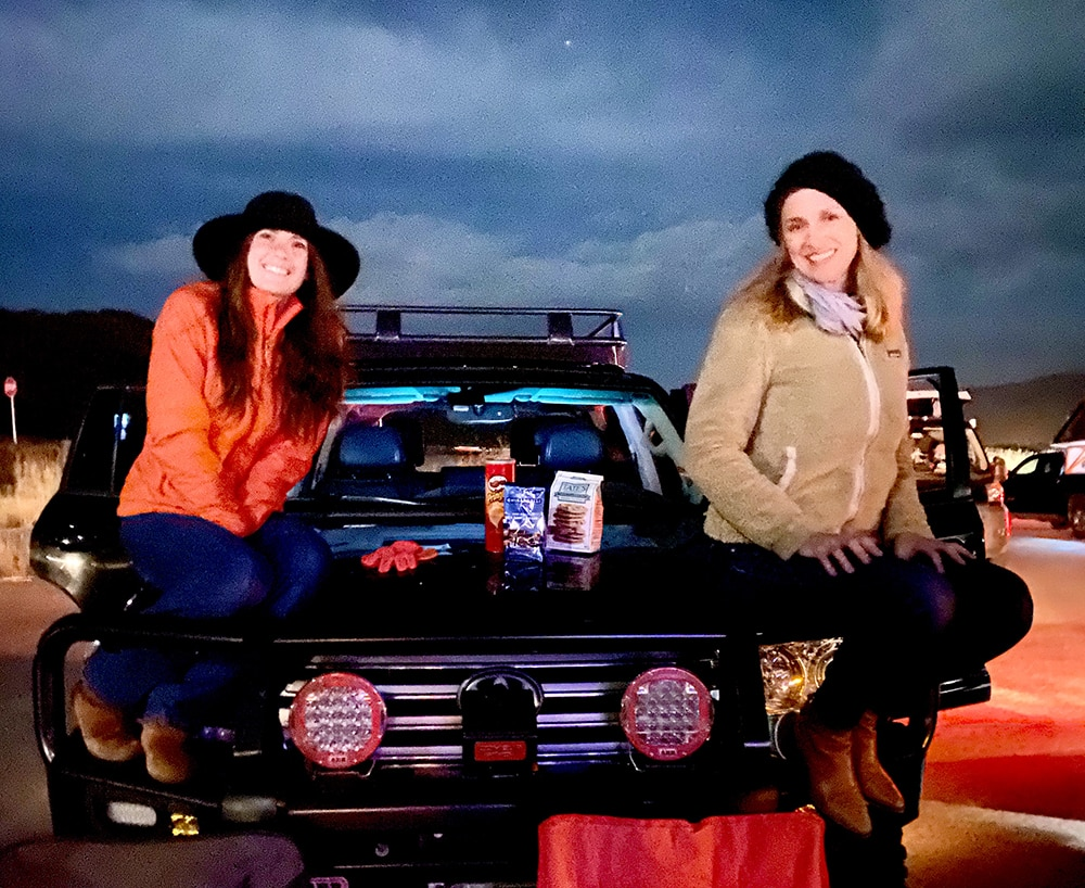 Rachel Stotts and Colleen Galbraith with prime movie seating on the hood of a friend's SUV.