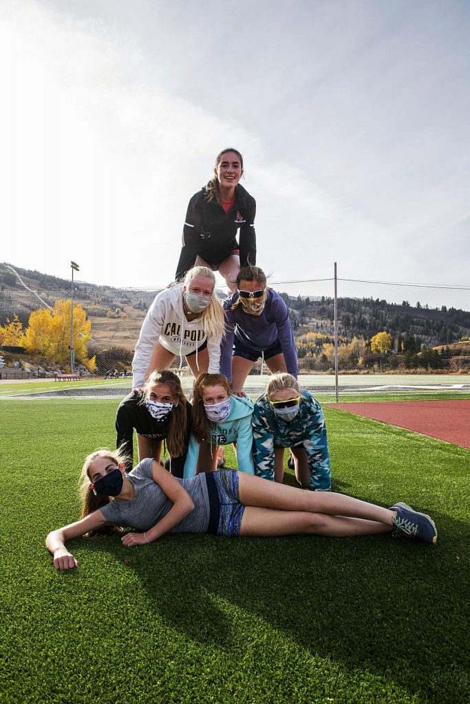 Aspen High School's girls cross country athletes pose in a pyramid formation on their home track on Thursday, Oct. 15, 2020. (Kelsey Brunner/The Aspen Times)