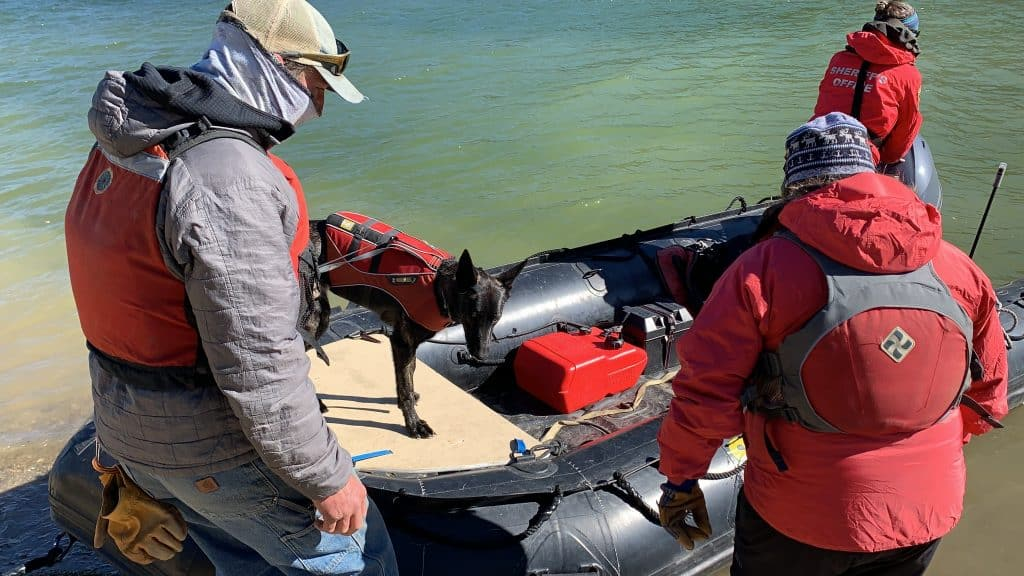Chris Brindisi and his Dutch shepherd Cache get ready to push off into the Dillon Reservoir to search for submerged divers on Oct. 14, 2020.