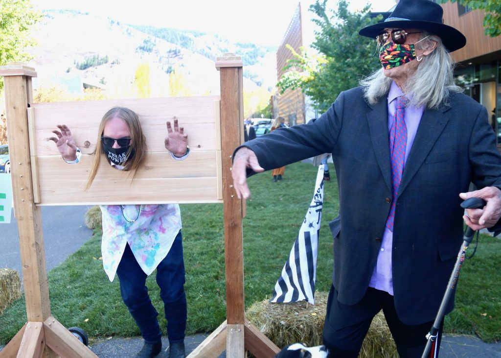 Daniel Joseph Watkins takes his turn in the stocks as former Pitkin County Sheriff Bob Braudis, right, looks on during the
