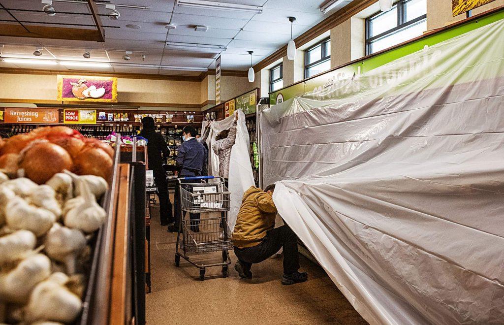 A shopper reaches under the plastic lining covering fresh produce in Aspen's City Market on Monday, Oct. 26, 2020. The store's employees were covering all refrigerated food with plastic to hold the refrigeration as long as possible and closed off the freezer sections with caution tape to deter shoppers from opening the doors.