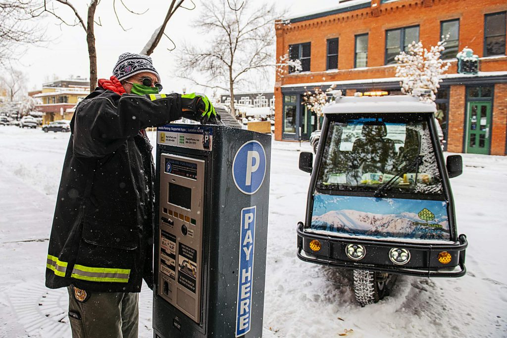 """City of Aspen's parking enforcement officer Greg Fitzpatrick scrapes snow and ice off the solar panel on top of the parking meter in downtown Aspen on Monday, Oct. 26, 2020. """"I have to clean off the panels so we get enough charge since it'll be a cloudy couple of days,"""" said Fitzpatrick."""