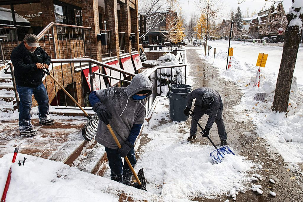 People shovel the walkway outside of Four Mountain Sports in Aspen on Monday, Oct. 26, 2020.