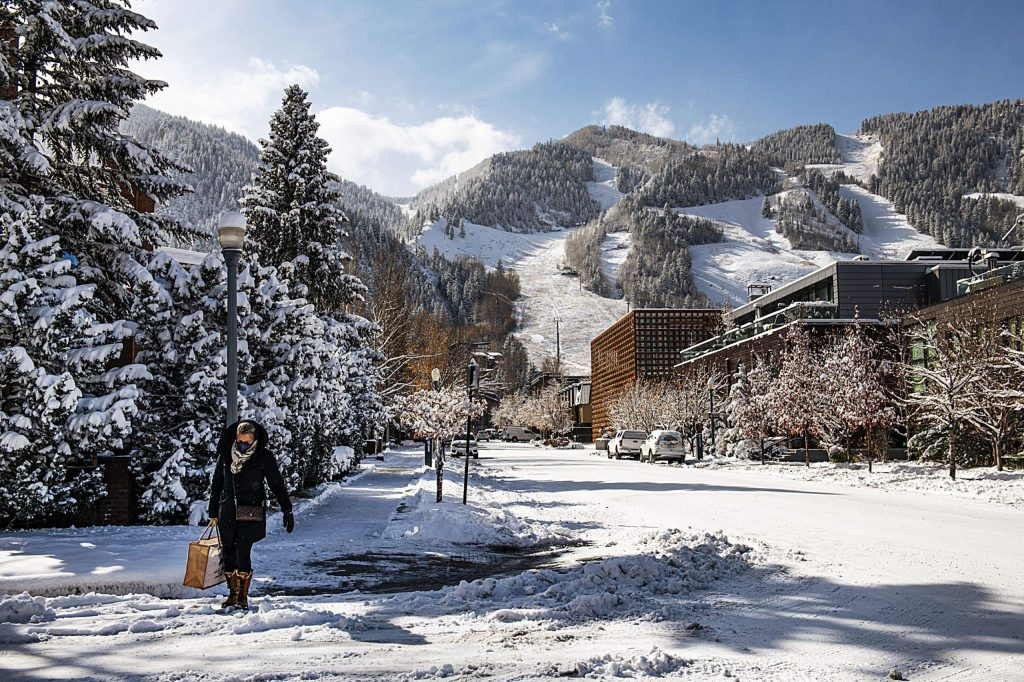 A woman carries her groceries home after a snowstorm in Aspen on Monday, Oct. 26, 2020.