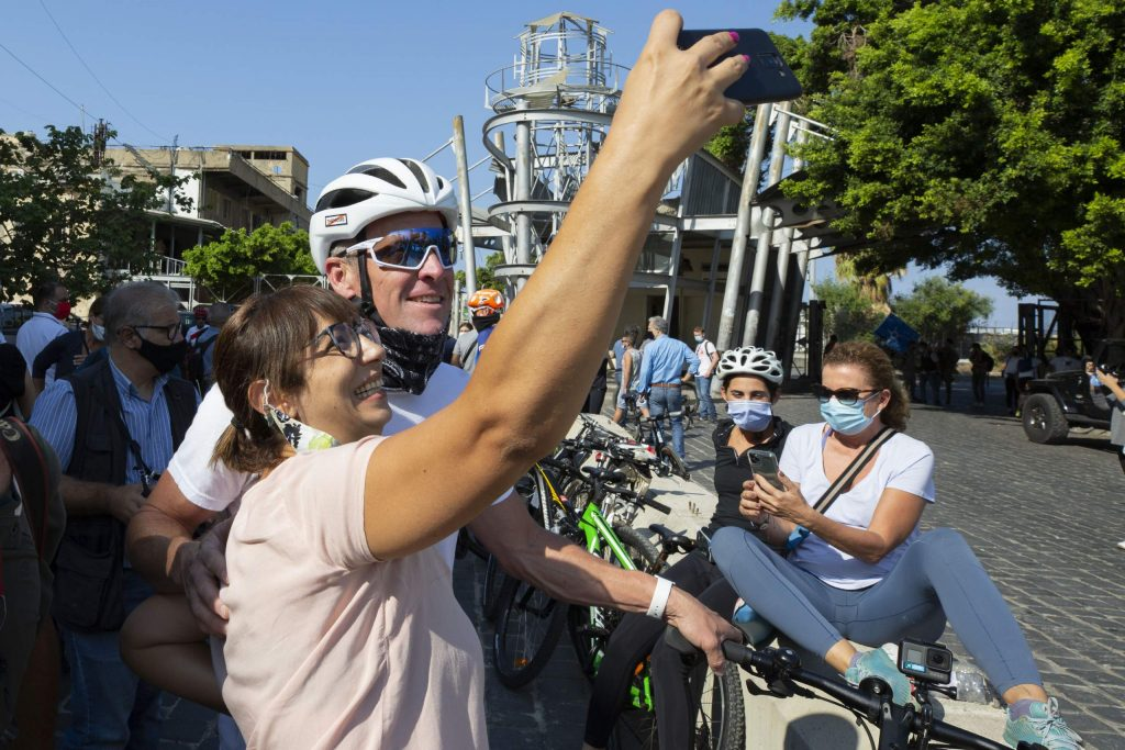 Former American professional cyclist Lance Armstrong, background, poses for a selfie before he rides with Lebanese and foreign cyclists at the site of the Aug. 4 deadly blast in the port of Beirut that killed scores and wounded thousands in Beirut, Lebanon, Sunday, Oct. 4, 2020. Armstrong led a charity bike tour named
