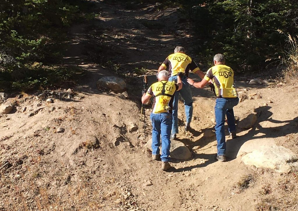 Paul and Kelly Harrison help plane crash survivor Rick Stephens hike up the steep Rocky Mountain grade to the site of the Wichita State University football team plane crash Stephens survived 50 years ago. Paul and Kelly's cousin Martin was a team equipment manager who died in the crash.