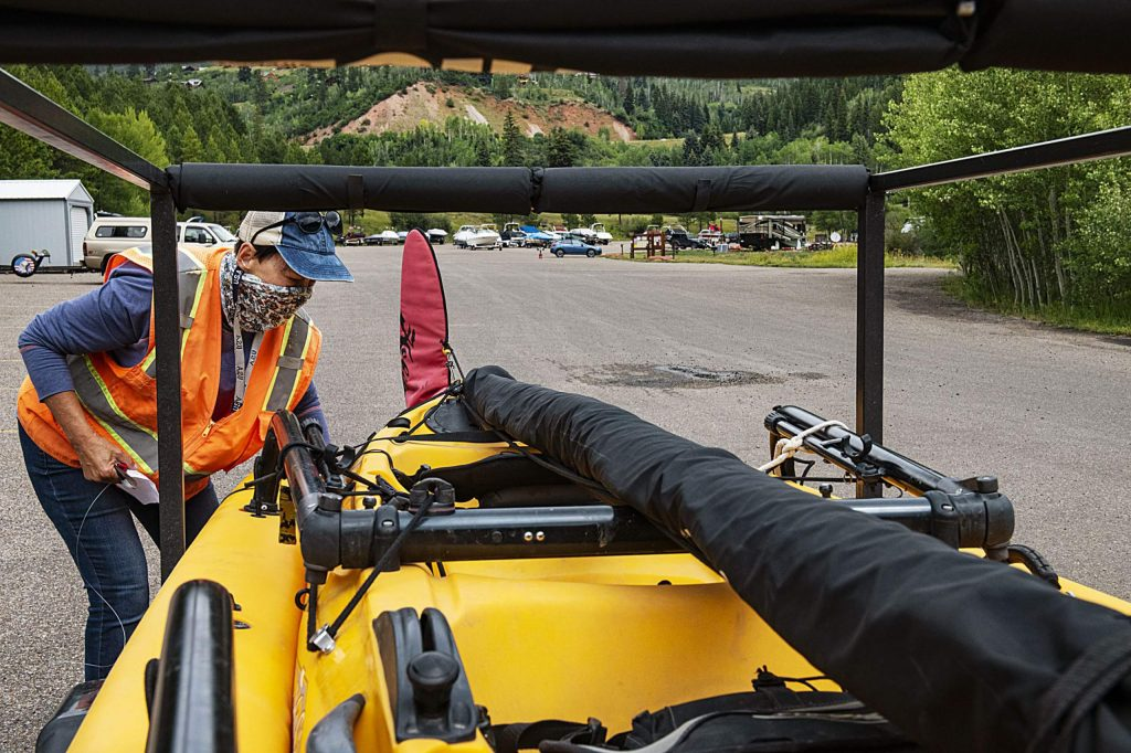 Jaime McCullah, site supervisor and boat inspector, walks around a boat as it checks-in before launching at Ruedi Reservoir on Friday, July 24, 2020. (Kelsey Brunner/The Aspen Times)