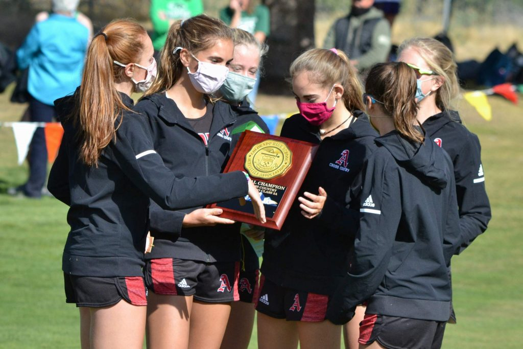 The Aspen High School girls cross country team celebrates after winning their Class 3A, Region 1 race on Friday, Oct. 9, 2020, at Hillcrest Golf Club in Durango. (Joel Priest/Courtesy of the Durango Herald)