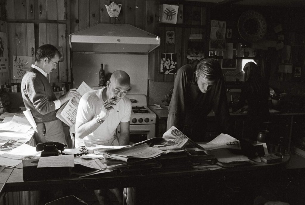 Hunter S. Thompson (center) reading newspapers with novelist William Kennedy (left) and campaign manager Ed Bastian during Thompson's 1970 campaign to be sheriff of Pitkin County.
