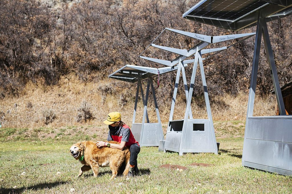A student from Aspen Community School pets dog, Emily, while learning about Skyhook Solar in Woody Creek on Tuesday, Oct. 20, 2020.