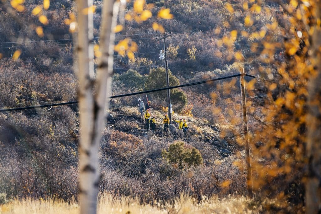 Aspen firefighters work to contain a small, slow-moving wildfire off of McLain Flats Road while Holy Cross Energy works on a power line in Aspen on Wednesday, Oct. 14, 2020. The fire was contained and extinguished quickly, only affecting a little more than one-tenth of an acre of land.