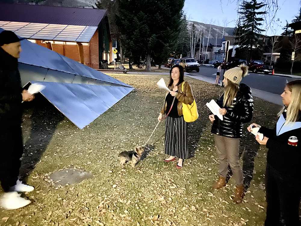Artist Griffin Loop, left, listens to guests as they read their intentions written on paper airplanes that were they sent flying into his stainless steel sculpture.