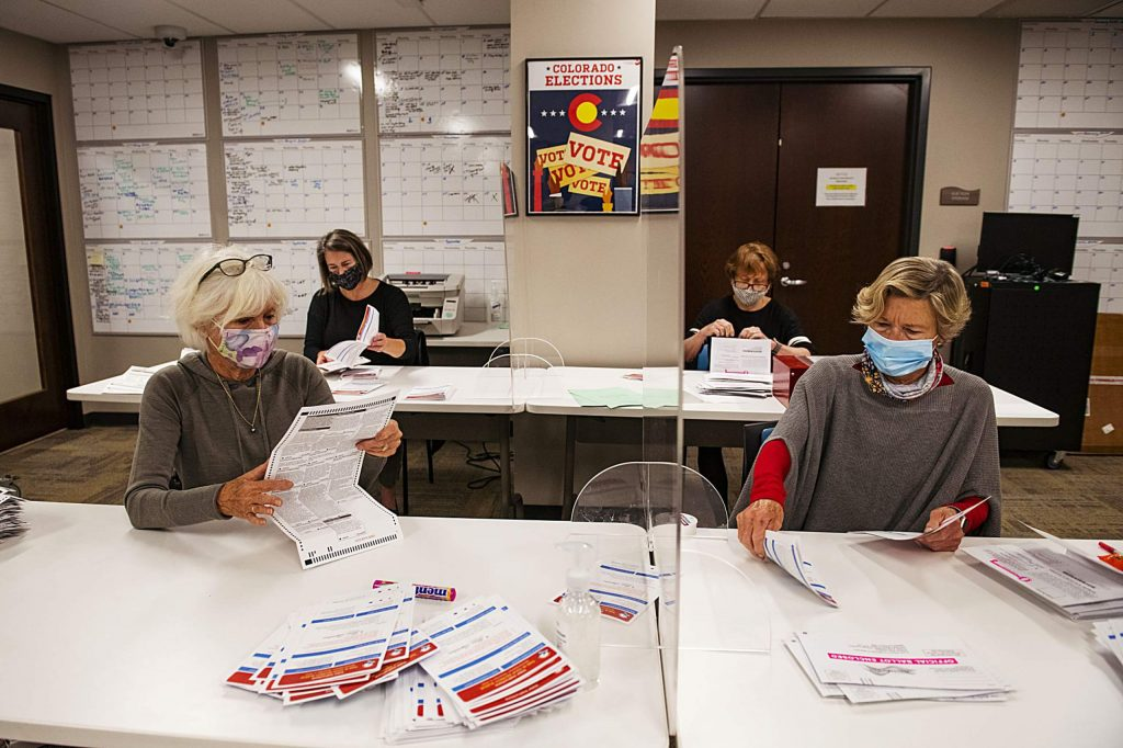 Carolyn Fieles, left, Suzy Meredith-Orr, Frieda Wallison, and Judy Dunn open ballots in the Pitkin County Administration Building on Election Day in Aspen on Tuesday, Nov. 3, 2020. The volunteers were checking that the ballots weren't stained and that they were labeled as Pitkin County ballots. (Kelsey Brunner/The Aspen Times)
