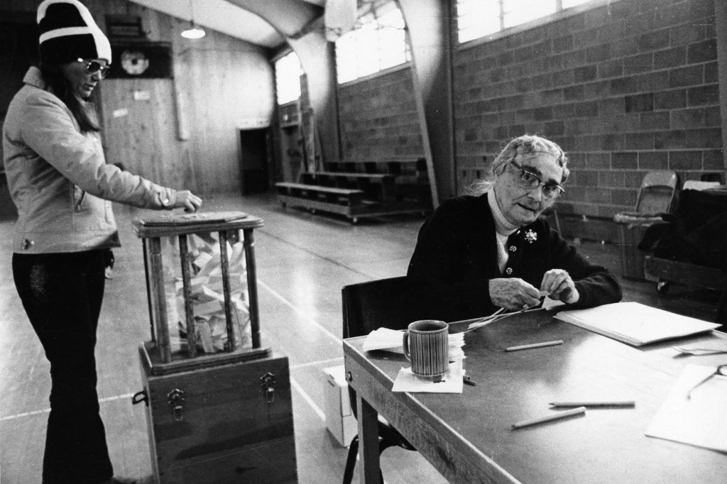 Marite Balderson voting while Maude Twining, an election judge, sits at a table in the Red Brick Building, circa 1975.