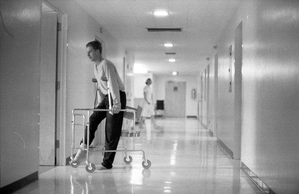 A patient with his foot in a cast using a walker in the halls at Aspen Valley Hospital, 1965.