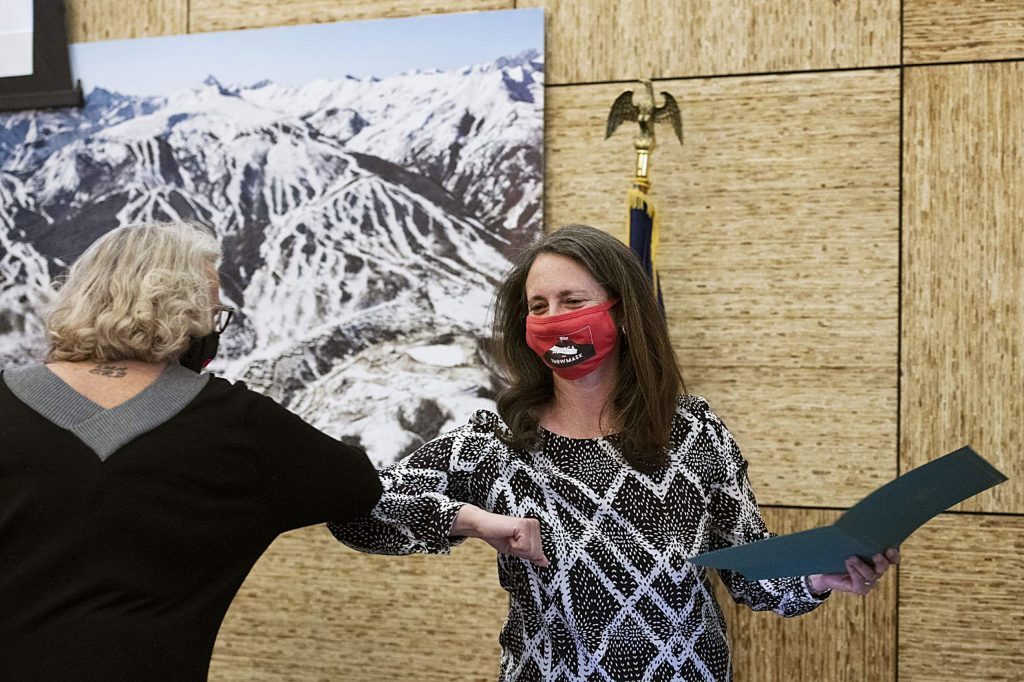 Alyssa Shenk, right, bumps elbows after being sworn in for another term on Snowmass Town Council in Town Hall on Monday, Nov. 16, 2020. (Kelsey Brunner/The Aspen Times)