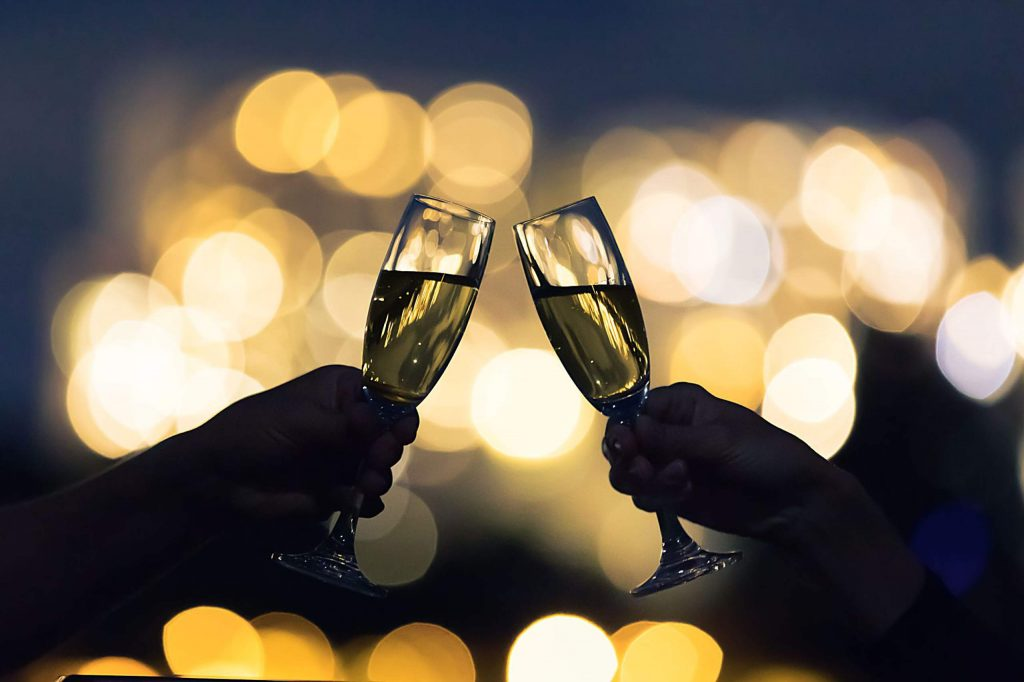 Couple toasting glasses of champagne agains a city night lights.